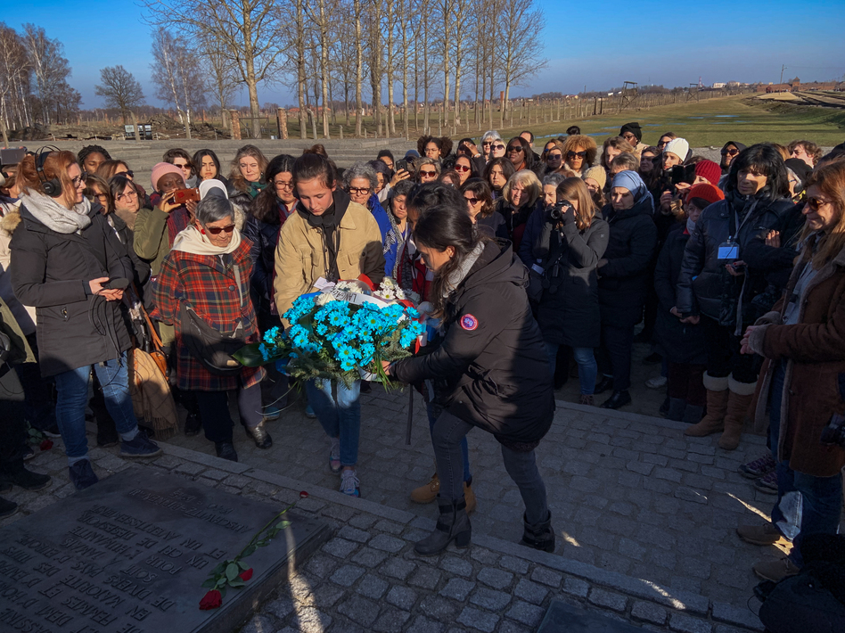 Members of a group of French women from diverse religious and ethnic backgrounds lay a wreath near the Auschwitz gas chambers earlier this month. After learning more about the horrors of the Holocaust, they hoped to bring greater understanding to their country riven by new acts of anti-Semitism. (Eleanor Beardsley/NPR)