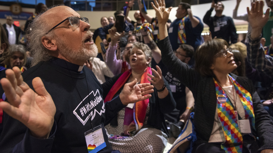 Protesters sing and pray outside the United Methodist Church's special session of the general conference in St. Louis on Tuesday. Delegates voted to maintain current rules against LGBTQ clergy and same-sex marriage. (Sid Hastings/AP)
