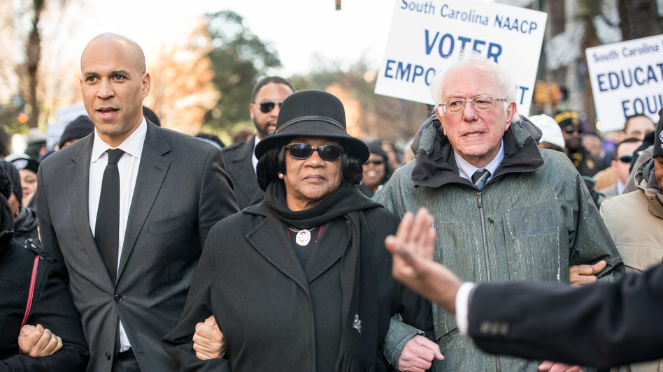 Sens. Cory Booker and Bernie Sanders, seen at a South Carolina NAACP march in January, are two of the 2020 Democratic presidential candidates pressed on the issue of reparations this week. (Sean Rayford/Getty Images)