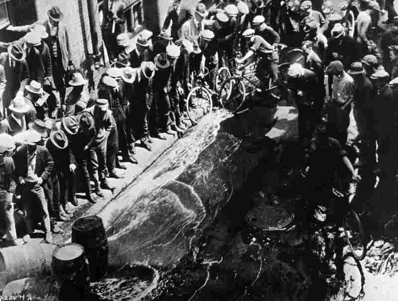 Contraband beer being spilled into the streets from barrels during the Prohibition era. During this time in New York City, approximately 30,000 illegal speakeasies were formed.
