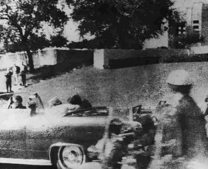 President John F. Kennedy is struck by an assassin's bullet as he travels through Dallas in a motorcade on November 22, 1963. The assassination became a sensationalized event that contributed to conspiracy theories which continue to circulate today.