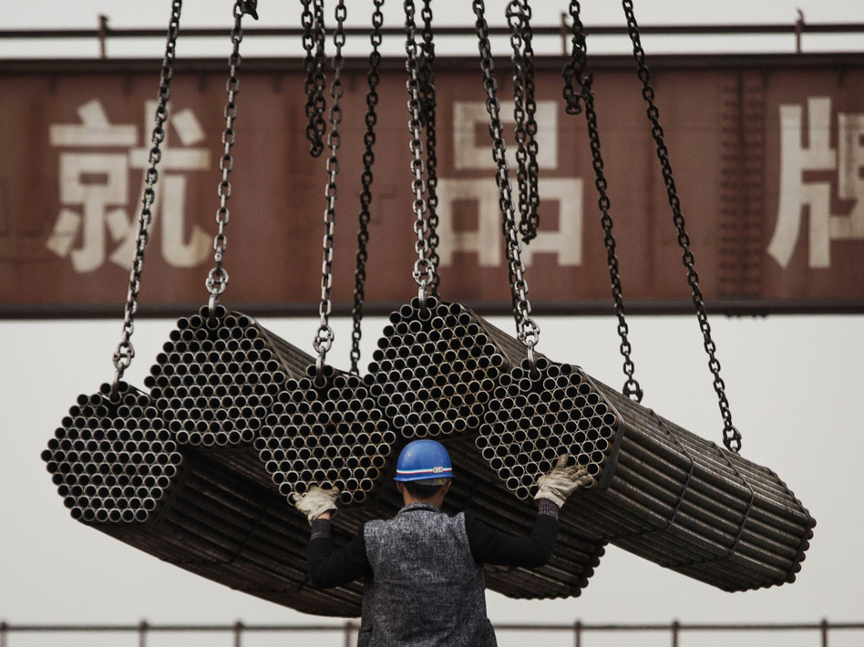 A worker helps load steel rods April 6, 2016, at a plant in Tangshan, in China's Hebei province. China's government plays a powerful role in how its businesses operate — giving them preferential treatment over their rivals. (Kevin Frayer/Getty Images)