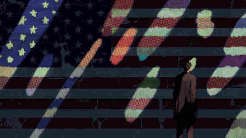 A man stands before the American flag.
