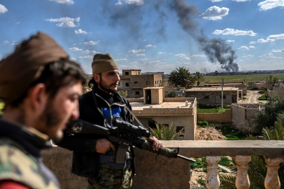 U.S.-backed fighters stand guard on a building during shelling of the Islamic State's last holdout in the town of Baghouz, Syria, on March 3. (Bulent Kilic/AFP/Getty Images)