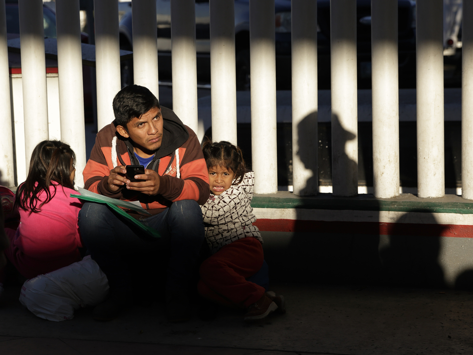 A migrant and his children wait to hear whether their number is called to apply for asylum in the United States, at the border in Tijuana, Mexico. (Gregory Bull/AP)