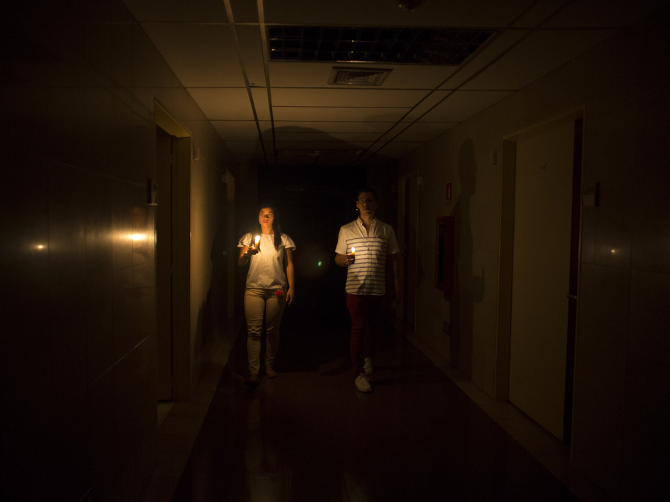 Amid a widespread power outage in Venezuela on Thursday, relatives of a patient walk in the dark halls of a health clinic in Caracas. (Ariana Cubillos/AP)