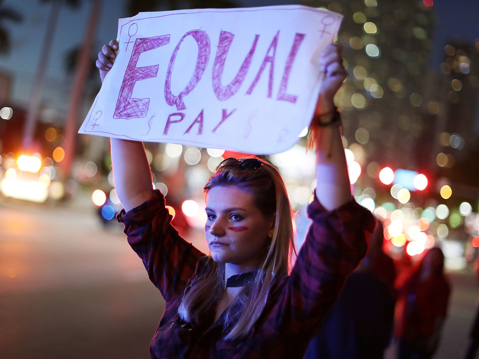 """Clarissa Horsfall joins with others during """"A Day Without A Woman"""" demonstration on March 8, 2017, in Miami. Employment attorneys say they've seen a spike in pay-disparity cases. (Joe Raedle/Getty Images)"""