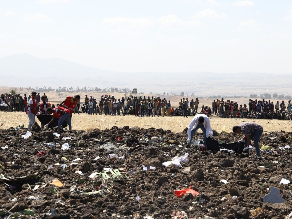 A rescue team collects remains of bodies amid debris at the crash site of Ethiopian Airlines Flight 302 near Bishoftu, a town some 37 miles southeast of Addis Ababa, Ethiopia, on Sunday. (Michael Tewelde/AFP/Getty Images)
