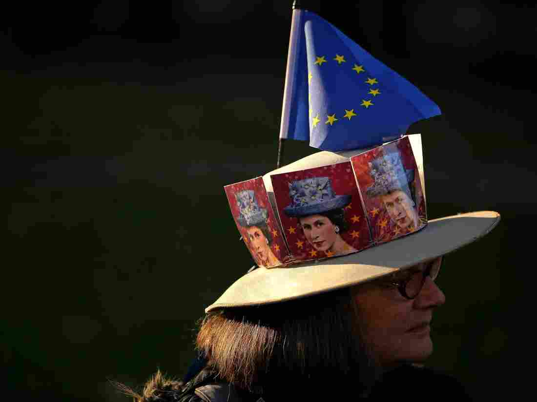 A pro-Brexit activist wears a hat decorated with pictures of Britain's Queen Elizabeth II and an EU flag as they demonstrate outside the Houses of Parliament in central London on February 27, 2019. (Photo by Daniel LEAL-OLIVAS / AFP) (Photo credit should read DANIEL LEAL-OLIVAS/AFP/Getty Images)