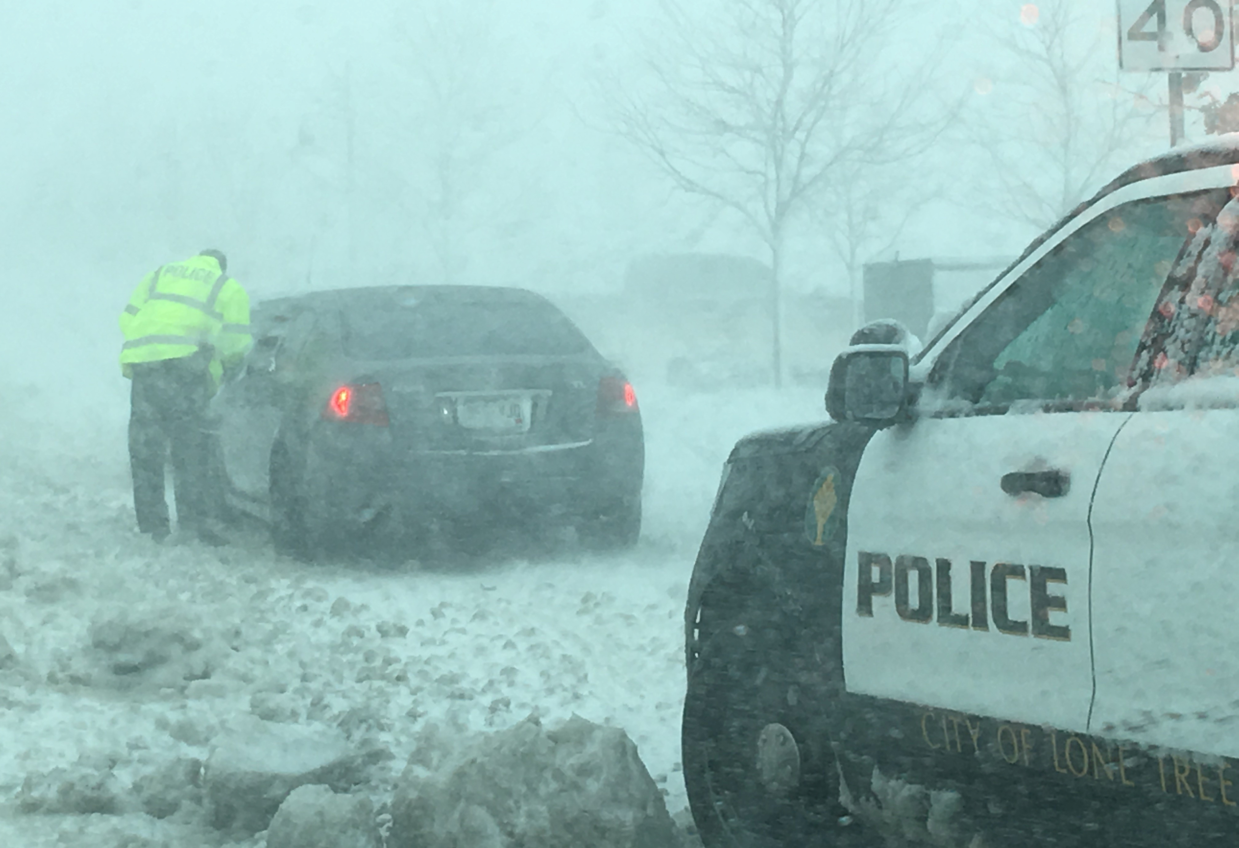 A policeman in Lone Tree, Colo., talks to a driver as snow clogs the towns roads, caught in a later winter storm known as a bomb cyclone.