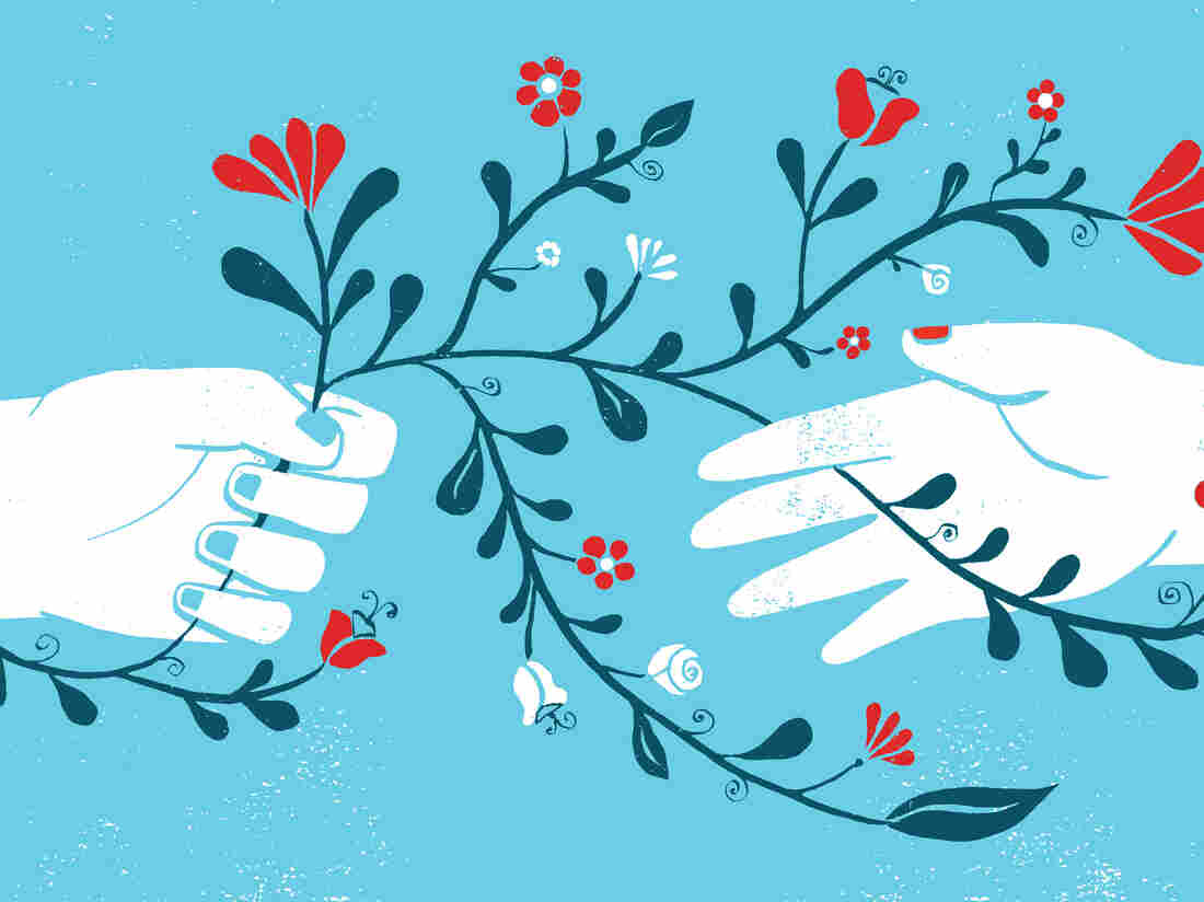 Image of two hands on a blue background. One hand is passing a plant with red flowers to the other hand.