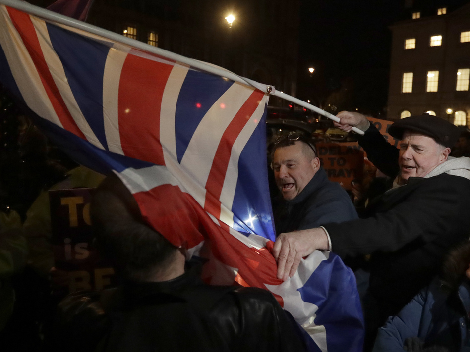 Brexit supporters and opponents shout at each other outside Parliament in London on Thursday, the day that British lawmakers voted to delay Brexit. (Matt Dunham/AP)