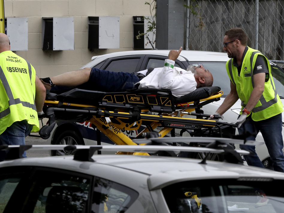 Ambulance staff take a man from outside a mosque in central Christchurch, New Zealand on Friday. Multiple people are in custody after shootings at two mosques there. (Mark Baker/AP)