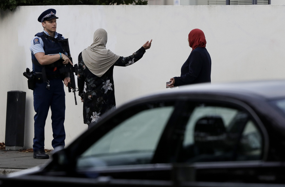 A police officer directs pedestrians near the site of one of the mass shootings at two mosques in Christchurch, New Zealand, on Saturday, March 16. (Mark Baker/AP)