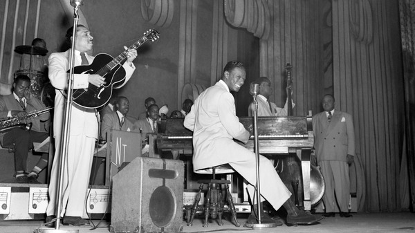 Nat King Cole plays with his jazz orchestra on the stage of The Apollo Theater, in Harlem, N.Y. in the 1950s.