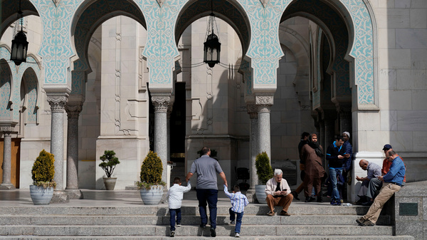 A man leads two young boys into Friday prayers as Muslim worshippers arrive for prayer following the mosque attacks in New Zealand at the Islamic Center of Washington in Washington.
