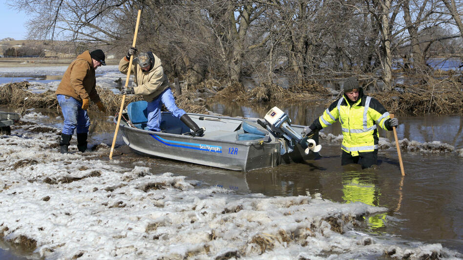 Tom Wilke, his son Chad, and Nick Kenny launch a boat into the swollen waters of the Elkhorn River to check on Wilke's flooded property, in Norfolk, Neb., on Friday, March 15. (Nati Harnik/AP)