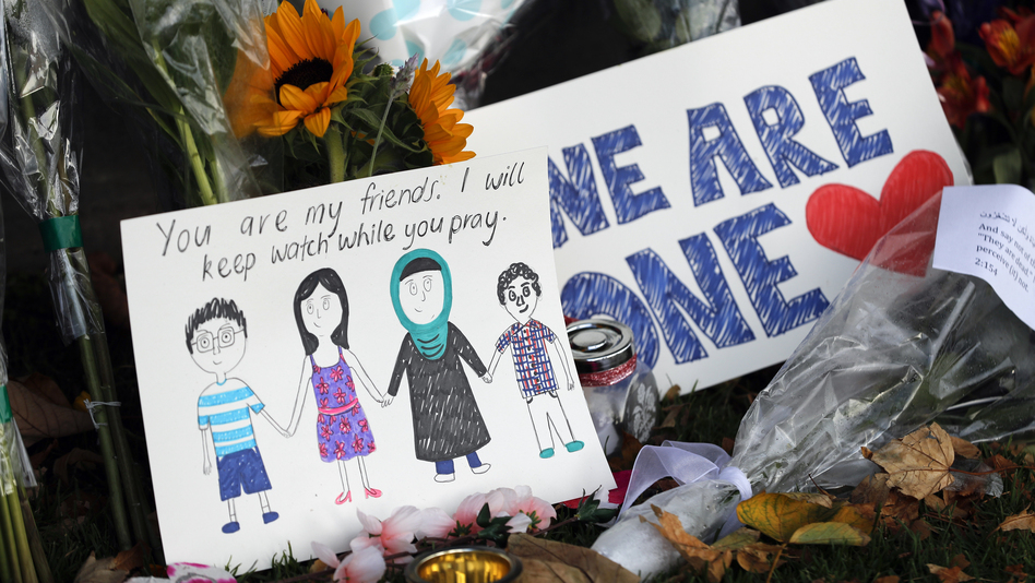 A message card sits among a collection of flowers left at the Christchurch Botanic Gardens in New Zealand on Saturday. A 28-year-old white supremacist accused in the mass shootings at two mosques that left dozens of people dead stood silently before a judge on Saturday. (Vincent Thian/AP)