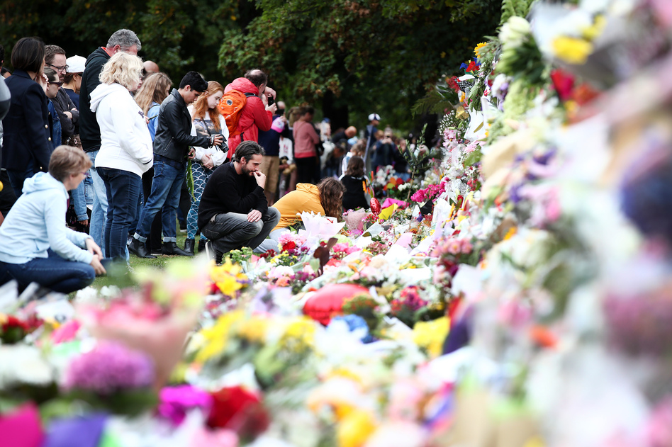 People lay flowers at a memorial for the mosque attack victims on Sunday in Christchurch, New Zealand. (Fiona Goodall/Getty Images)