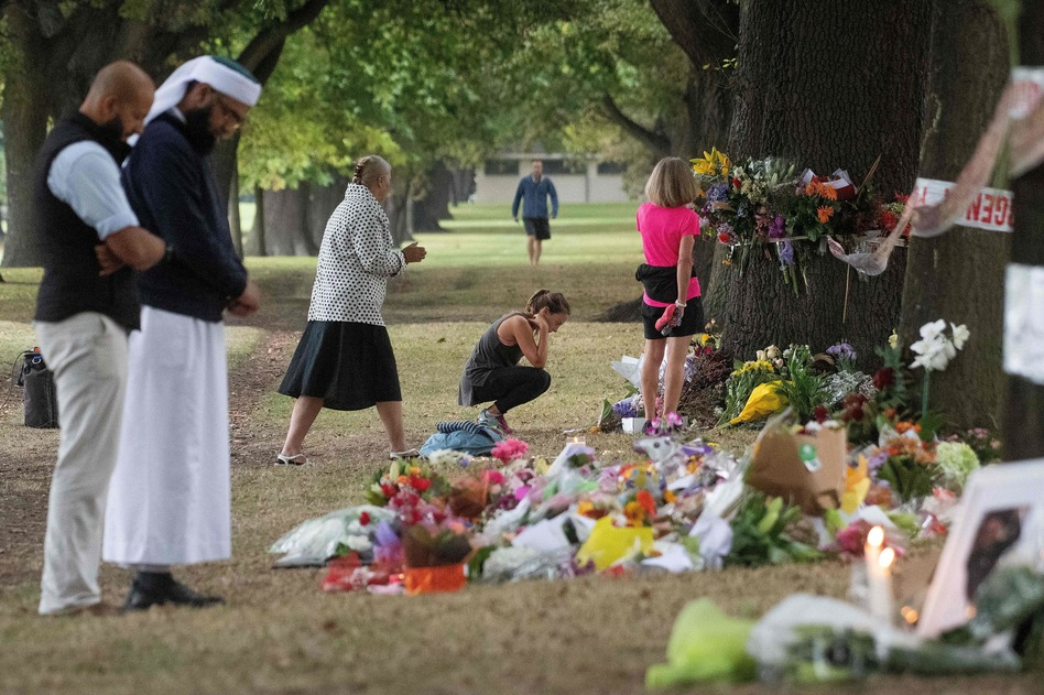 People on Tuesday stand next to floral tributes placed across the road from the Al Noor Mosque in Christchurch, New Zealand, where dozens of worshippers were gunned down last week. (Marty Melville/AFP/Getty Images)