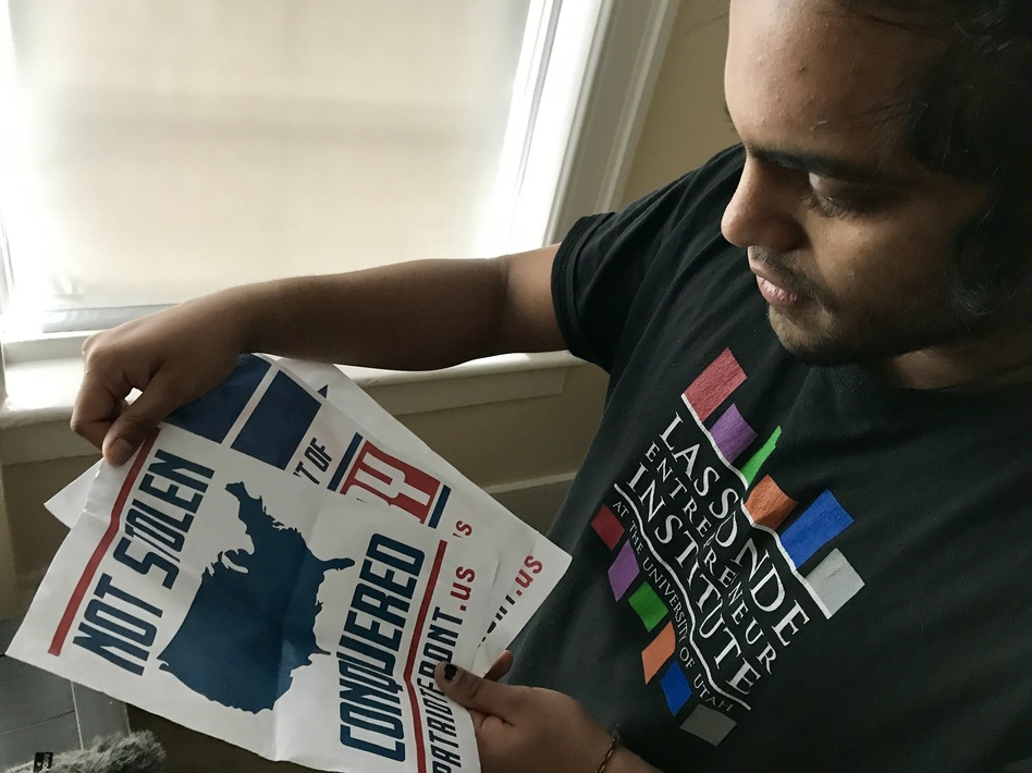 Mohan Sudabattula, a senior at the University of Utah, shows posters he found on campus from the white nationalist group Patriot Front. (Nate Hegyi/KUER)