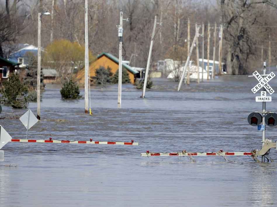A railroad crossing is flooded with water from the Platte River in Plattsmouth, Neb. Record high floodwaters inundated regions of the Midwest following an intense winter storm and rapid snowmelt. (Nati Harnik/AP)