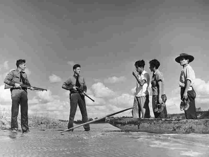 Two armed American border guards deter a group of undocumented immigrants from attempting to cross a river from Mexico into the United States in 1948. Prior to the 20th century, the border between the two countries was porous and not extensively patrolled.