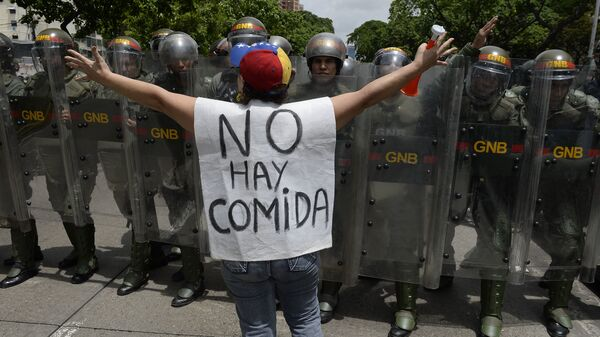 """A woman with a sign reading """"There is no food"""" protests against new emergency powers decreed this week by President Nicolas Maduro in front of a line of policemen in Caracas on May 18, 2016. / AFP / FEDERICO PARRA (Photo credit should read FEDERICO PARRA/AFP/Getty Images)"""