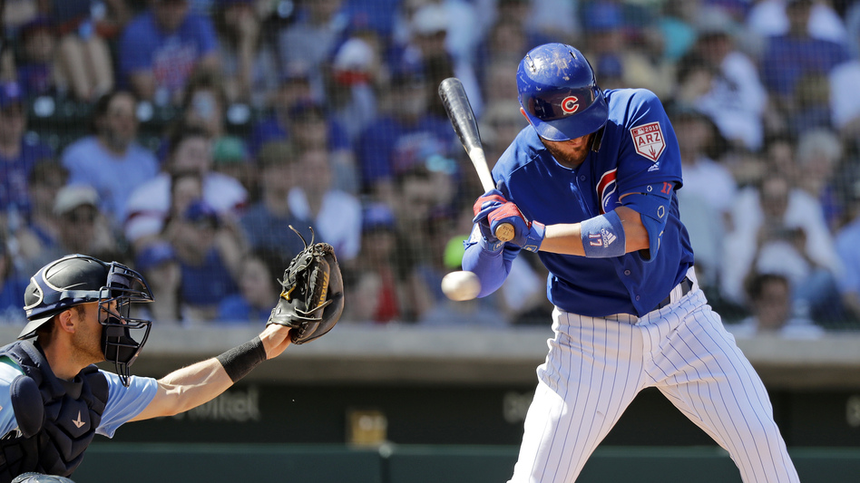 Chicago Cubs' Kris Bryant, right, is hit by a pitch as Seattle Mariners catcher Austin Nola looks on at a spring training baseball game on Tuesday. (Elaine Thompson/AP)