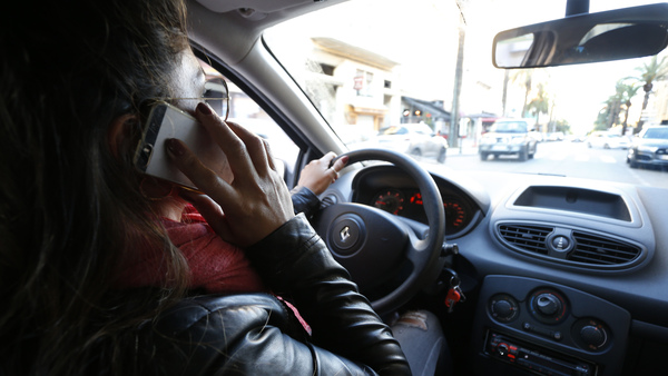 A woman speaks on her phone while driving. Both drivers and walkers use cell data 4,000 percent more than they did in 2008, which means they aren