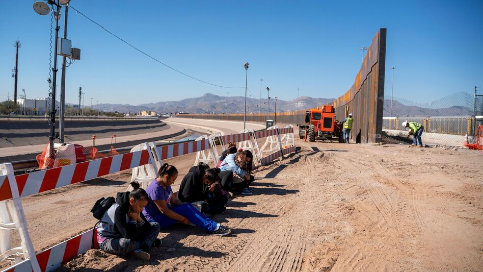 Salvadoran migrants wait for transportation after turning themselves in to U.S. Border Patrol agents in El Paso, Texas — where a border fence is under construction. The Pentagon says it will spend up to $1 billion to help build the fence. (Paul Ratje /AFP/Getty Images)