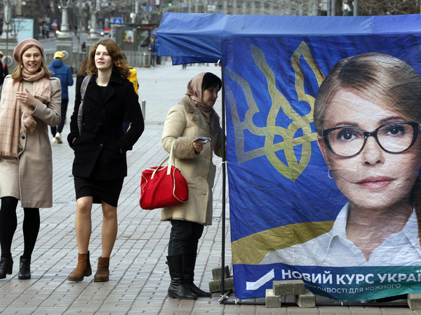 Passersby walk past a tent in support of former Prime Minister Yulia Tymoshenko in Kiev on March 26. None of the 39 presidential hopefuls are expected to win an outright majority in Sunday's vote, meaning a likely runoff.