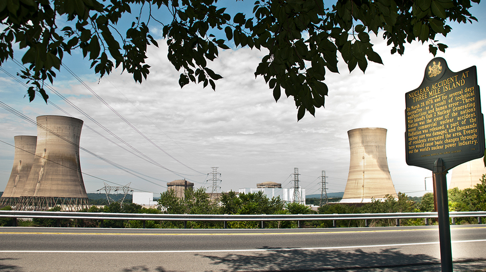 A historical marker commemorates the 1979 nuclear accident at Three Mile Island — the most serious in U.S. history. To the left are the cooling towers for the mothballed Unit 2 reactor, which partially melted down. (Joanne Cassaro/WITF)