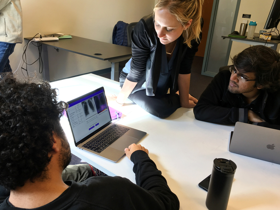 Amir Kiani (from left), Chloe O'Connell and Nishit Asnani troubleshoot an algorithm to diagnose tuberculosis in computer lab at Stanford University. (Richard Harris/NPR)