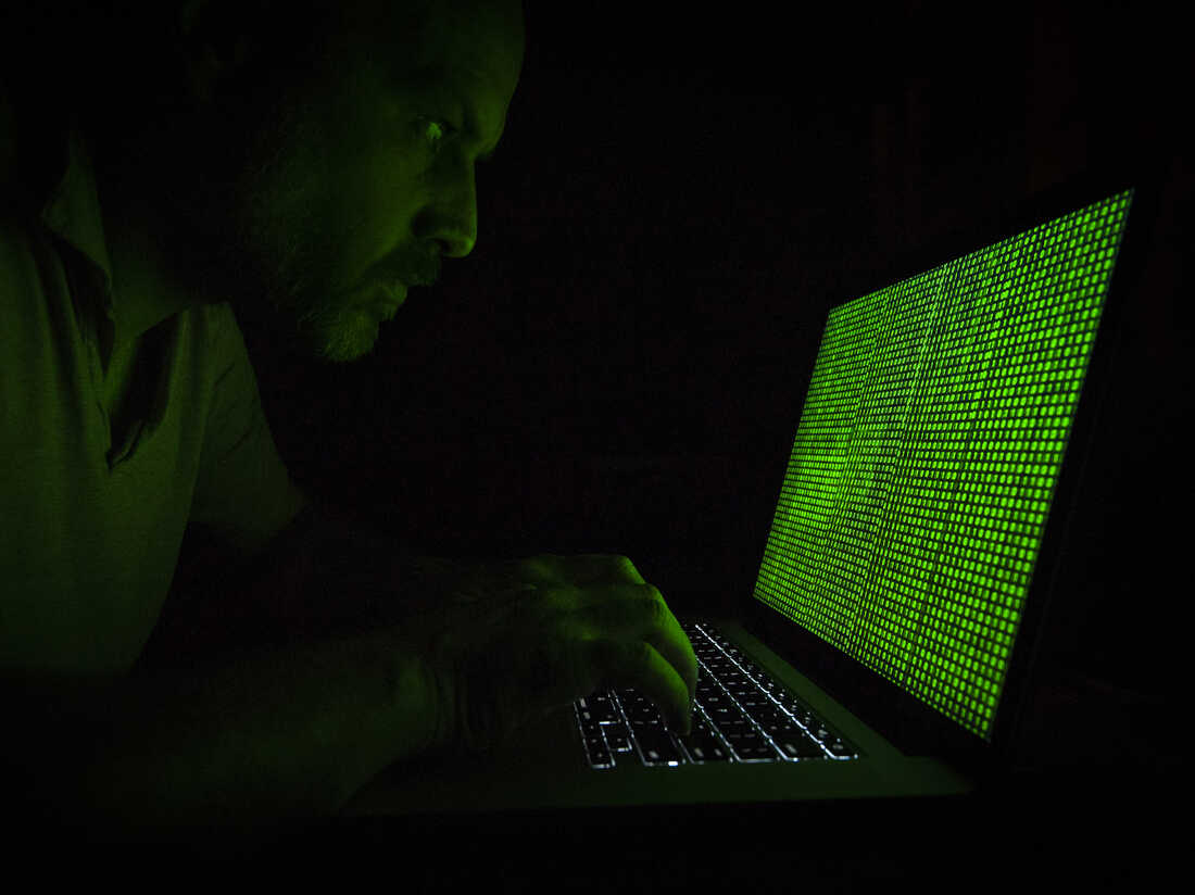 A man is seen portraying a hacker with binary code symbols on a laptop.
