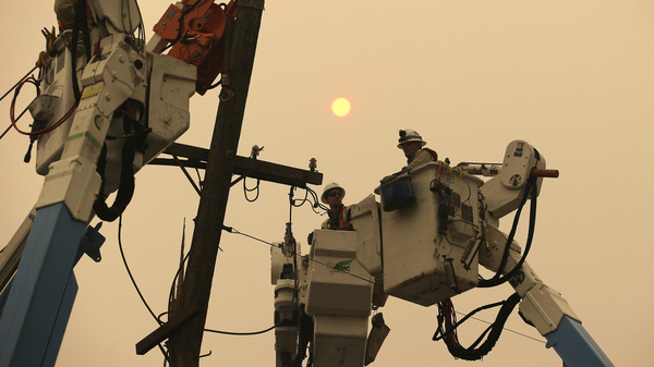 PG&E crews work to restore power lines in Paradise, Calif., after the Camp Fire destroyed much of the Northern California town.