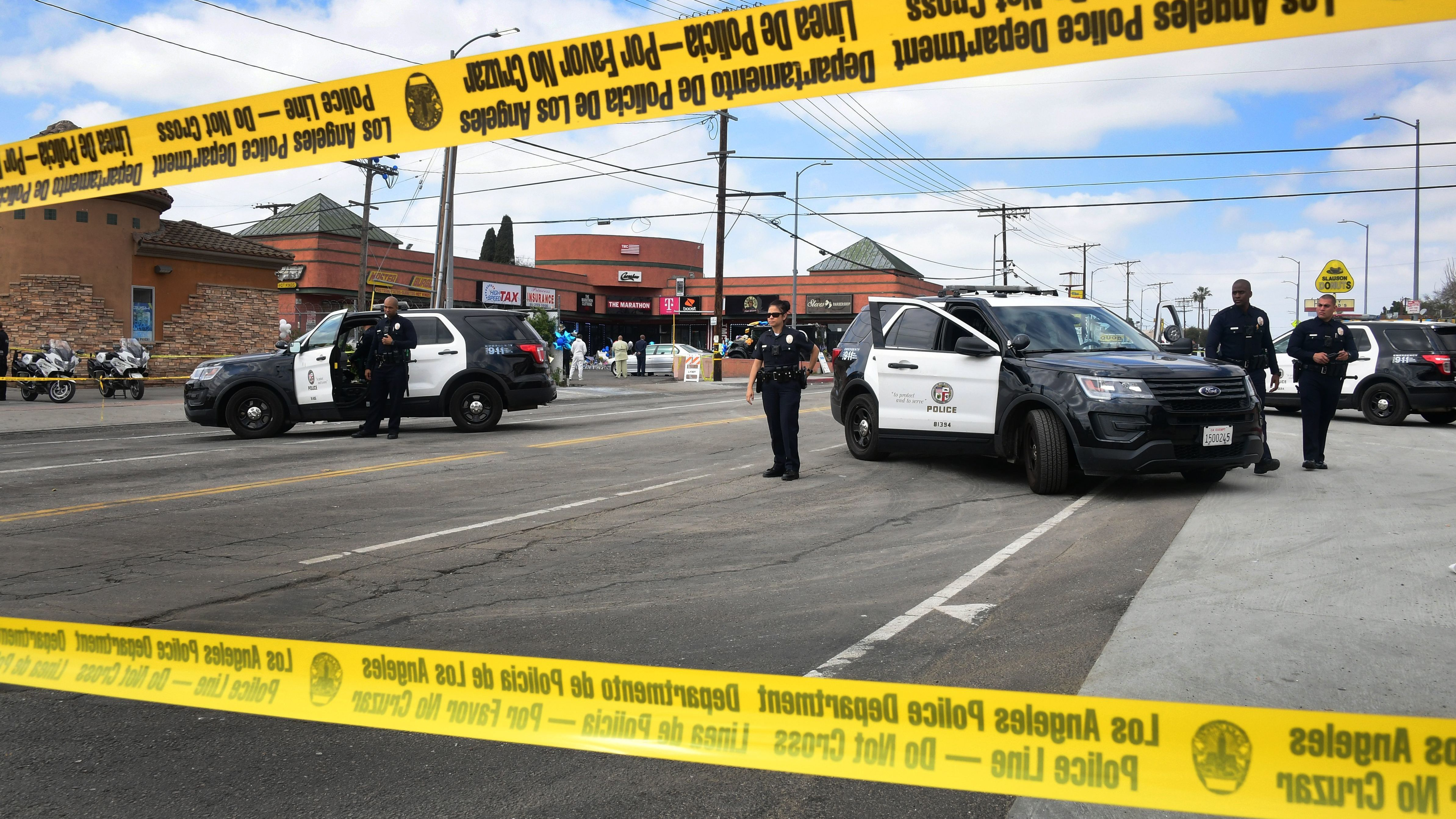 Police monitor a roadblock in front of the late Nipsey Hussle's The Marathon Store in Los Angeles on Tuesday. Authorities announced the arrest of the shooting suspect in the rapper's death.