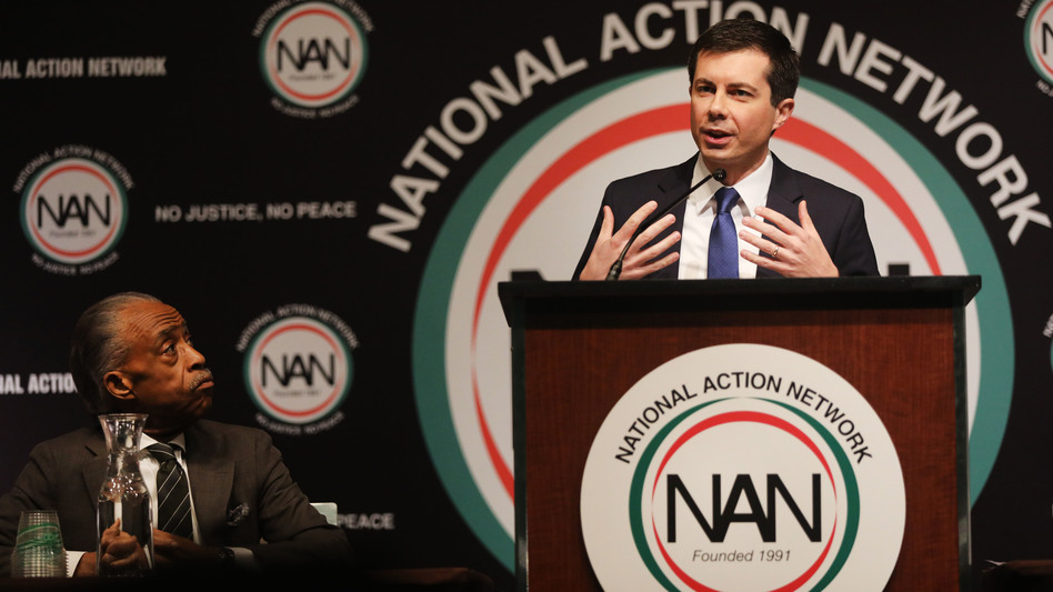 With the Rev. Al Sharpton looking on, Democratic presidential hopeful South Bend, Ind., Mayor Pete Buttigieg speaks at the National Action Network's annual convention Friday in New York City. (Spencer Platt/Getty Images)