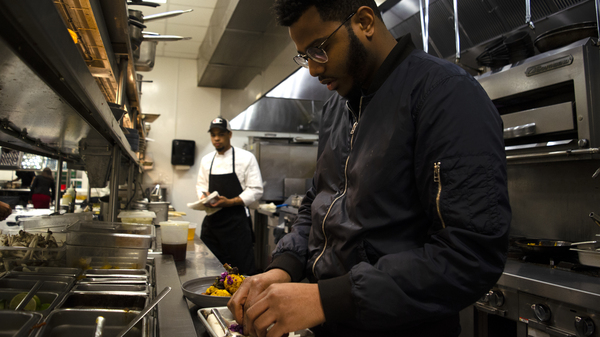 Onwuachi cooks in the kitchen of his D.C. restaurant, Kith and Kin. His food encompasses a range of African, Caribbean, African-American and other influences.