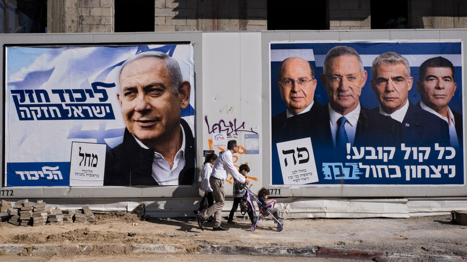 People walk by election campaign billboards showing Israeli Prime Minister and head of the Likud party Benjamin Netanyahu (left) alongside the Blue and White party leaders, including Benny Gantz. Ahead of Tuesday's election, Netanyahu has pledged to annex Israeli settlements in the occupied West Bank. (Oded Balilty/AP)