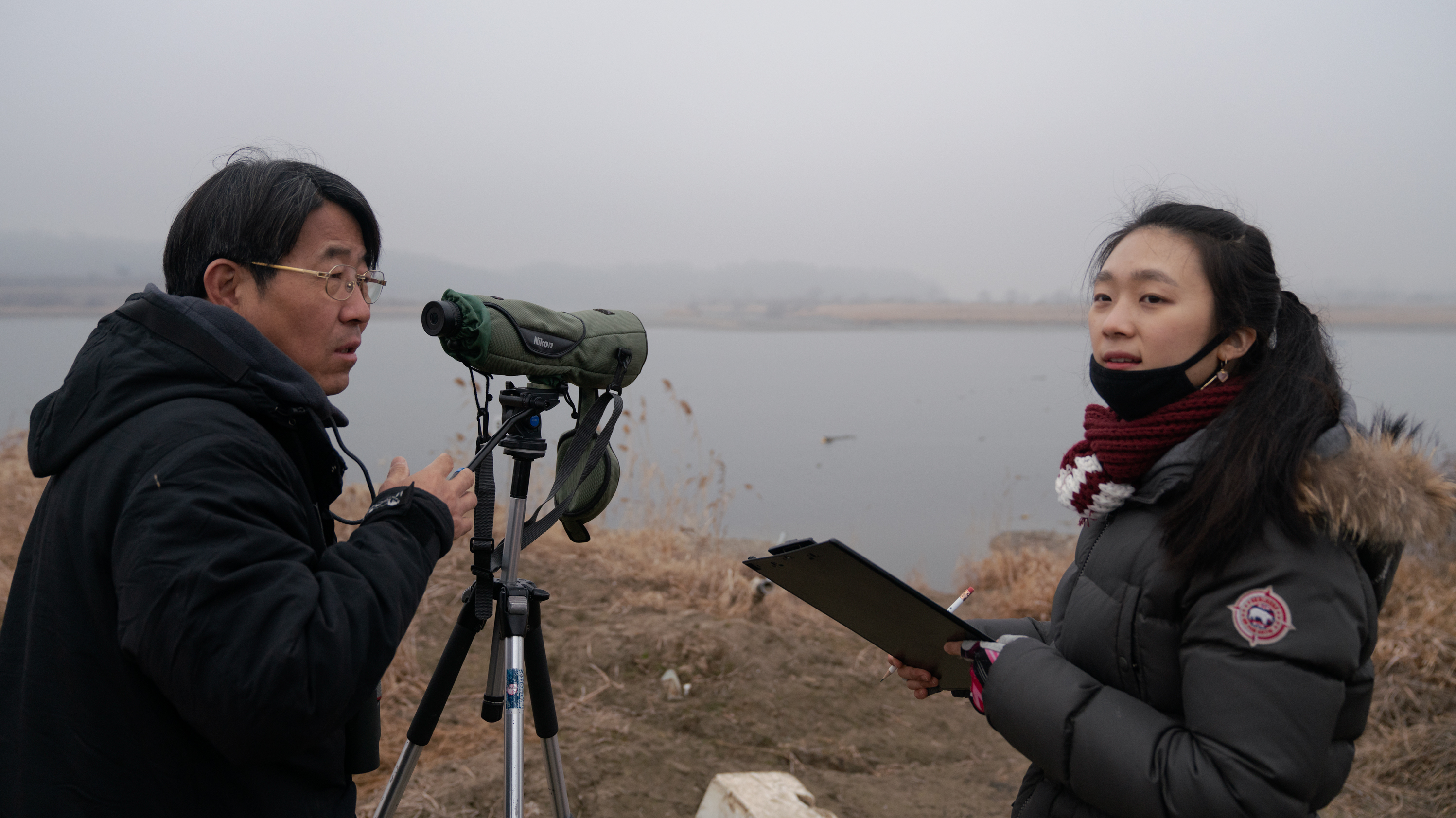 Kim Seung-ho (left), the director of the DMZ Ecology Research Institute, counts birds of the DMZ with intern Pyo Gina.