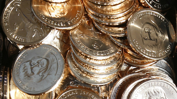 A pile of newly minted $1 coins honoring former President Thomas Jefferson are unveiled by the U.S. Mint in Washington, D.C., in 2007. In a turnaround, congressional analysts are no longer recommending a phaseout of paper dollars in favor of a dollar coin.