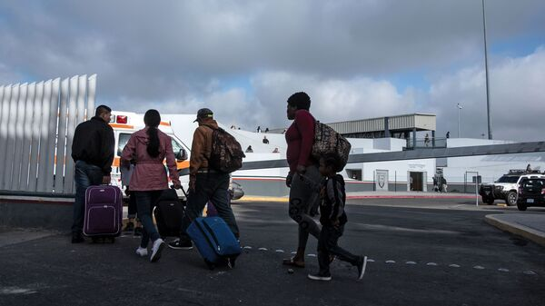Asylum-seekers walk at El Chaparral Port of Entry to present themselves to U.S. border authorities to request asylum, in Tijuana, Baja California state, Mexico, on Tuesday.