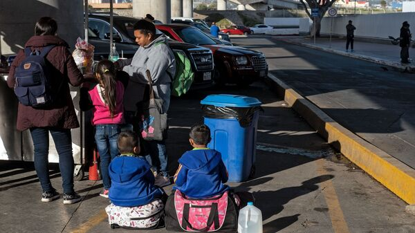 Asylum-seekers eat outside El Chaparral Port of Entry as they wait for to present themselves to U.S. border authorities to request asylum, in Tijuana, Baja California state, Mexico, on Tuesday.