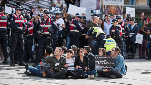 Animal rights protesters link arms to block an intersection in the central business district of Melbourne, Australia, on Monday.