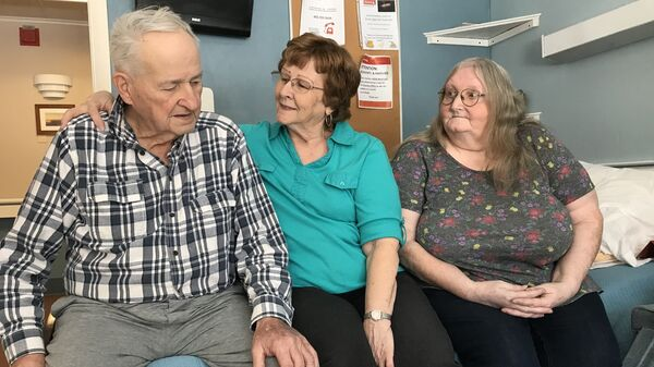 Joan Bousquet of Irasburg (center) has visited her husband Robert Bousquet at the Bel-Aire Center, a nursing home in Newport, Vt., every day since his long-delayed arrival. Diane Bapp of Barton, a family friend, often joins them.