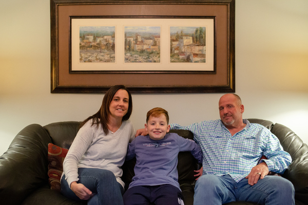 Jessica and Chris Calise sit in their living room with their son, Joseph Calise.
