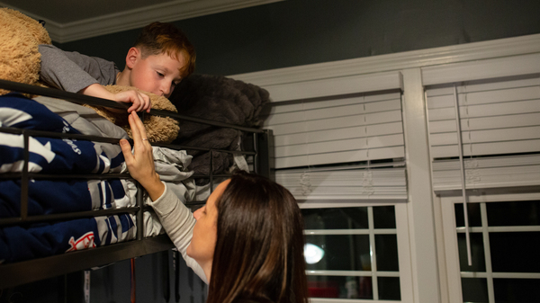 Jessica Calise checks on Joseph as he gets ready for bed. Joseph used to be afraid to sleep alone, but he has learned to be OK with it since his mother learned new parenting approaches.
