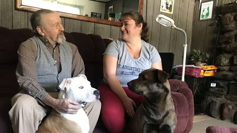 David Calderwood and Crystal Abel of Newport, Vt., sit with Abel's dogs Mike (left) and Zoe. David lives in Crystal's house, and she helps him with his medications and medical needs. He pays room and board, and Abel is also compensated by the state with Medicaid dollars. (Emily Corwin/Vermont Public Radio)