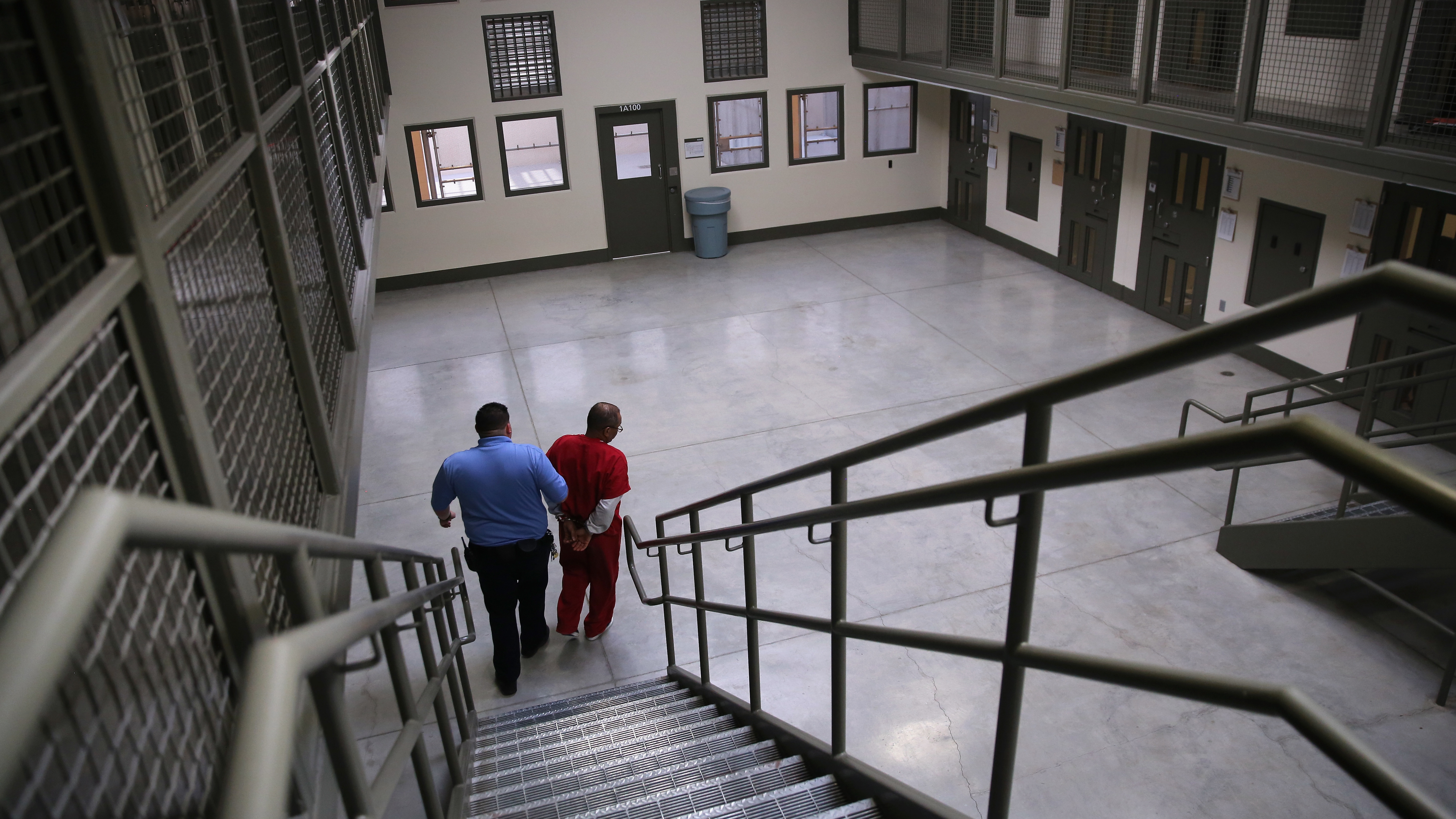 "A guard escorts a detained immigrant from his ""segregation cell"" back into the general population at the Adelanto Detention Facility in November 2013. Today the privately run ICE facility in Adelanto, Calif., houses nearly 2,000 men and women and has come under sharp criticism by the California attorney general and other investigators for health and safety problems."
